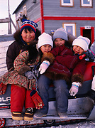 Jason Ahmaogak, Sophia Ahmaogak, Lorraine Tagarook and Krystle Ahmaogak on seat of the family's Polaris snowmobile, village of Wainwright, Arctic Coast west of Barrow, Alaska.