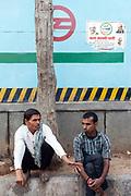 Men talk beneath a political poster fort the Aam Aadmi Party, Vasant Vihar, New Delhi, India