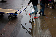 A delivery on a trolley, crossing over a puddle after rainfall in Oxford Street, central London.