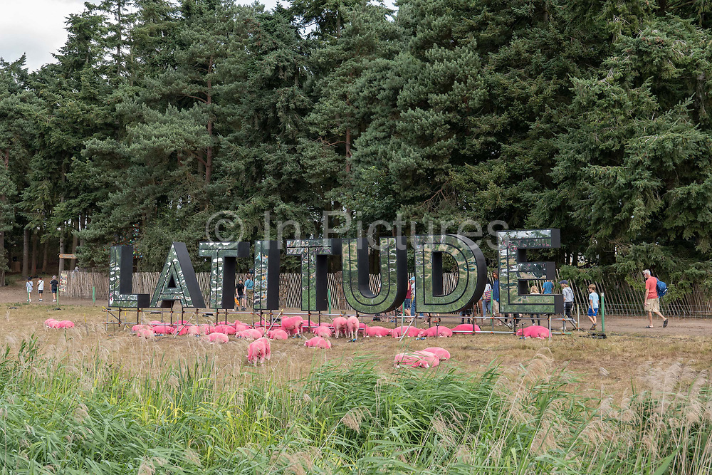 Sheep coloured pink gather near a huge Latitude Festival sign on the 21st July 2019 in Southwold in the United Kingdom.