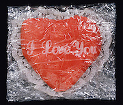 Heart cushion with -I love you- text wrapped in plastic food wrap