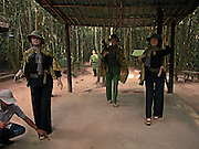 """Vietnam, Cu Chi, viet women guerrilla. visitors are greeted by a sign reading: """"Please try to be a Cu Chi guerrilla. Wear these uniforms before entering tunnel."""" Black pajamas, pith helmets, rubber sandals and old rifles are available."""