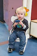Nederland, Veghel, 20101117.?Kind op de creche. Hij leest een plaatjesboek. Kijkt in de camera. .Kinderopvang 't Kroontje in Veghel...Netherlands, Veghel, 20101117. ?Child at the nursery. He reads a picture book. Looks into the camera..Childcare t Kroontje in Veghel..