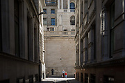 People walk beneath the high walls outside the Bank of England during the 2018 heatwave in the City of London, the capitals historic financial district, on 2nd August 2018, in London, England.