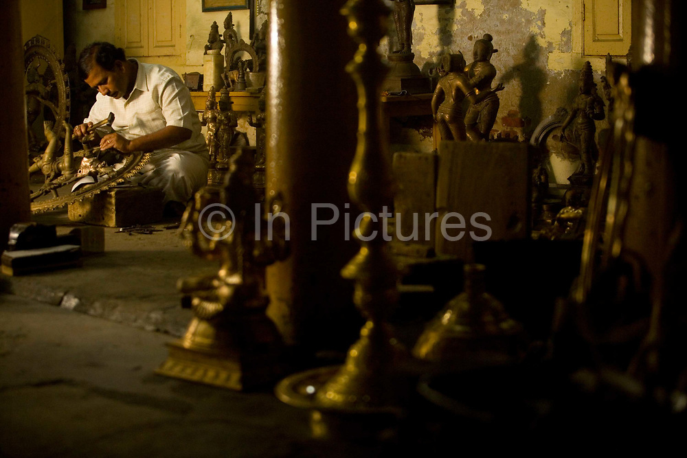 Master craftsman Radhakhrishna Stpathy, works on the final touches to a statue of the dancing Nataraja at dawn in his workshop in Swamimalai, India.The current Stpathy family is the twenty third generation of bronze casters dating back to the founding of the Chola Empire. The Stapathys had been sculptors of stone idols at the time of Rajaraja 1 (AD985-1014) but were called to Tanjore to learn bronze casting. Their methods using the ,ƒÚlost wax,ƒÙ process remains unchanged to this day..