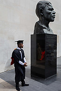 A young black graduate stands beneath the bust of Nelson Mandela after his graduation eremony, in celebration of his university academic achievement, outside the Festival Hall, on 20th July 2017, on the Southbank, London, England.