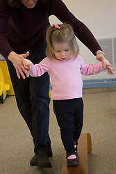 United States, Washington, Bellevue, woman helping girl on balance beam at Kindering Center