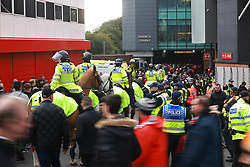 © Licensed to London News Pictures. 24/10/2021. Manchester, UK. Police operation to separate the different teams' fans as they arrive and prevent disorder . Football fans outside Old Trafford ahead of a Premier League tie between Manchester United and Liverpool . Photo credit: Joel Goodman/LNP
