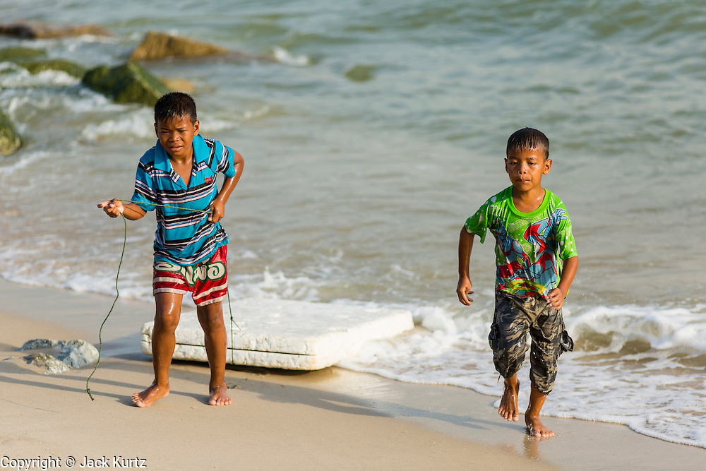 07 FEBRUARY 2014 - KAO SENG, SONGKHLA, THAILAND:  Children whose fathers are fishermen, run up the beach in Kao Seng. Kao Seng is a traditional Muslim fishing village on the Gulf of Siam near the town of Songkhla, in the province of Songkhla. In general, their boats go about 4AM and come back in about 9AM. Sometimes the small boats are kept in port because of heavy seas or bad storms.     PHOTO BY JACK KURTZ