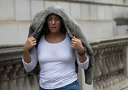 © Licensed to London News Pictures. 10/09/2021. A woman shelters form the rain underneath her jacket in Westminster, central London.. Thunderstorms are expected across parts of the UK following a period of warm weather earlier this week. Photo credit: Ben Cawthra/LNP