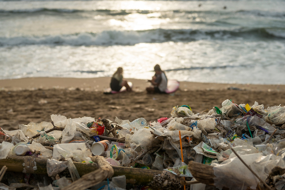 Bali, Indonesia - February 9, 2017: Two surfers sit on their surfboards at sunset as, in the foreground, trash that has washed up on the beach sits in a pile in Kuta, Bali.
