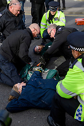 "© Licensed to London News Pictures. 19/11/2016. Heathrow, UK. Police use cutting equipment to detach an activist form a road surface. A group of activists stage attach themselves to a road surrounding  Heathrow Airport, during a demonstration against the expansion of Heathrow Airport and the building of a third runway. Some activists  threatened ""direct action"". Photo credit: Ben Cawthra/LNP"