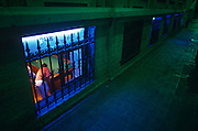 """Seen from street level at night, a pool player beolow pots a snooker ball in a downstairs pub in Nice on the the Cote d""""Azur"""