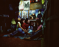 Portrait of Gina Andrade, 36, with her mixed Filipino-Japanese children Fatima Villagracia, 16, Kayceline Andrade, 10 and Alexandra Nicole Andrade, 10, relax inside their home in Laguna, Philippines on Dec. 2006.  Gina works as a tailor with the Development Action for Women Network, DAWN, an aid organization aimed at providing skills for Filipino women who worked Japan. Many of the women employed by DAWN left the Philippines to work as entertainers in Japan. Several were later sexually abused, coerced into prostitution and now have children with Japanese fathers.