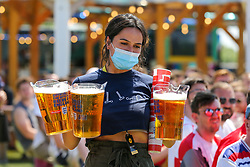 © Licensed to London News Pictures. 13/06/2021. London, UK. A staff member wearing a face covering with buckets of beer for fans at Skylight Rooftop, Tobacco Dock in London as they watch England's opening Euro 2020 game. Photo credit: Dinendra Haria/LNP