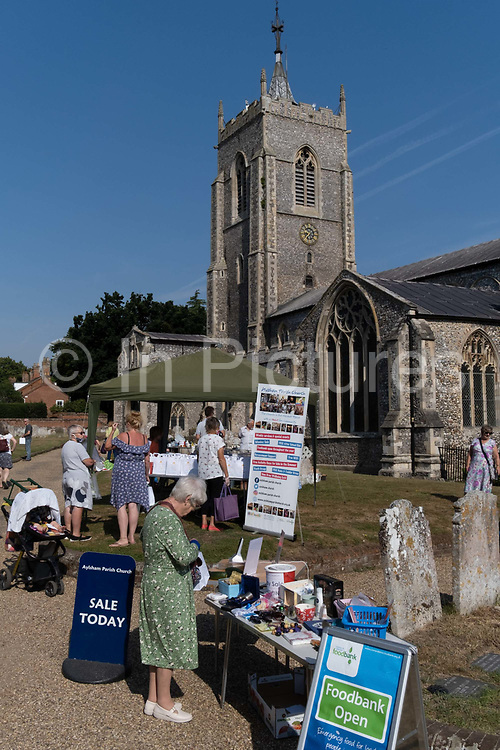 Members of the local parish community attend a churchyard market, an event helping raise funds outside the Church of St. Michael, on 10th August 2020, in Aylsham, Norfolk, England. The Church of St Michael and all Angels, Aylsham, is a church of medieval origins that was built in the 14th century under the patronage of John of Gaunt, lord of the manor of Aylsham.
