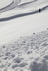 View of powdered snow with person standing by ski-tracks