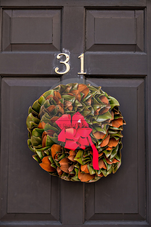 A magnolia Christmas wreath decorates the wooden door of a historic home on Church Street in Charleston, South Carolina.
