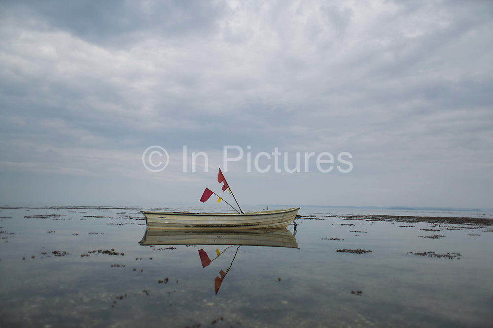 A small fishermans boat is anchored on calm shallow waters in the Bay of Århus. The boat and red flags are reflected in the water amongst the sea weeds. The East coast of Denmark is often calm and only really fished by small fishermens boats.