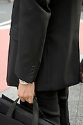 close up of a man standing in a business suit holding a briefcase
