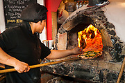 Pizza being baked in oven fired by lenga beech tree wood, Puerto Natales, Patagonia, Chile.