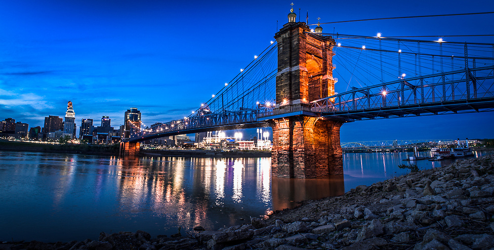 The John A. Roebling bridge is seen at blue hour as downtown Cincinnati looms in the background. As seen from the Covington, Kentucky side of the Ohio River.
