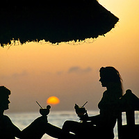 Cozumel, Mexico, vacation sunset.  Couple relax and enjoy the setting sun with cold drinks and conversation on the water unde a palapa.