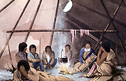 Interior of Cree Indian tent. Man smoking: Papoose in 'cradle': Cooking pot suspended over fire. From John Franklin 'Narrative of a Journey to the Shores of the Polar Sea'', London, 1823. Coloured lithograph.