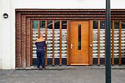 Nederland, the netherlands, Nijmegen, 23-10-2020 Een postbode bezorgt de post bij een appartementencomplex .Foto: ANP/ Hollandse Hoogte/  Flip Franssen