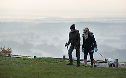 © Licensed to London News Pictures. 22/11/2018. Dorking, UK. Dog walkers on Box Hill near Dorking - as mist and frost cover the valley below. Photo credit: Peter Macdiarmid/LNP