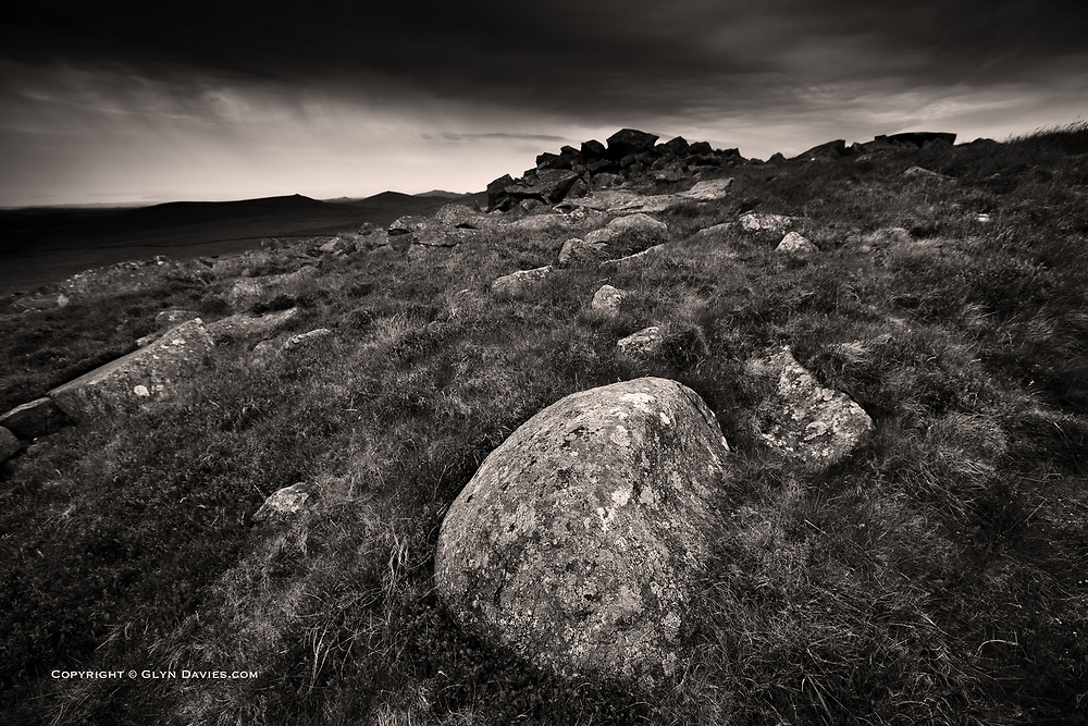 Retreating off the summit as huge sheets of rain swept across the peninsula, a most beautiful rounded granite boulder stood proud against the dark stunted vegetation all round. The wind ruffled the grasses as drops of rain started spitting in my face and then the stone sphere glistened under a torrential downpour, just one of millions in it's own process of shaping and growing older.