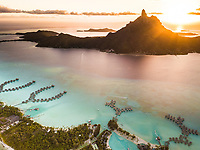 Aerial view of Bora Bora with red sunset light on Mount Otemanu in French Polynesia.