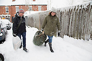 People taking home their Christmas tree in Kings Heath head out to enjoy the heavy snow fall on Sunday 10th December 2017 in Birmingham, United Kingdom. Deep snow arrived in much of the UK, closing roads and making driving treacherous, while many people simply enjoyed the weather.