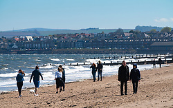 Portobello beach and promenade near Edinburgh during Coronavirus lockdown on 19 April 2020. People walking on beach.