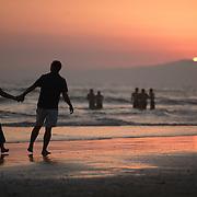 Strolling the beach at Huntington Beach as the sun sets over the Pacific Ocean.