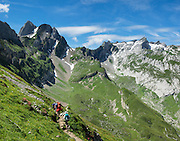 Hikers at Bötzel pass contemplate the distant peak of Santis, in Switzerland, Europe. Shared by three cantons, Säntis (2502 m) is the highest mountain in the Alpstein massif of northeastern Switzerland, and highest of the Appenzell Alps, which rise between Lake Walen and Lake Constance. Accessible via cable car or spectacular trails, Säntis provides a spectacular view across six countries: Switzerland, Germany, Austria, Liechtenstein, France and Italy. This image was stitched from multiple overlapping photos.