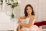 Little girl sits by the white piano. White flowers on the piano. Girl model in beautiful dress.