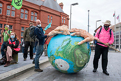 "© Licensed to London News Pictures;02/09/2020; Cardiff, Wales, UK. Extinction Rebellion protest in Cardiff Bay in front of the Senedd, the Welsh Government building, in support of the upcoming Climate and Ecological Emergency Bill. Today the protest is ""Rising Tide Action!!"" focusing on the impact that the climate crisis is having locally and across Wales because it is impacting weather cycles, flooding, air pollution and our food security. The protest involved arts, theatre, speakers, music, banners and a drown in. The protest is part of a national protest over the next two weeks including London and other cities in the UK against climate change. XR say that despite clear scientific evidence of the deadly climate and ecological emergency, the UK government are refusing to take the urgent action needed to avoid mass extinction, and that politicians need to support the Climate and Ecological Emergency Bill. During the coronavirus covid-19 pandemic, climate change is being forgotten but it is still an emergency that is happening. The protest was socially distanced and participants wore masks. Photo credit: Simon Chapman/LNP."