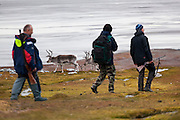 Researchers (carrying rifles for protection from polar bears) walk past reindeer (Rangifer tarandus) on the coast near Hyttevika, Svalbard.