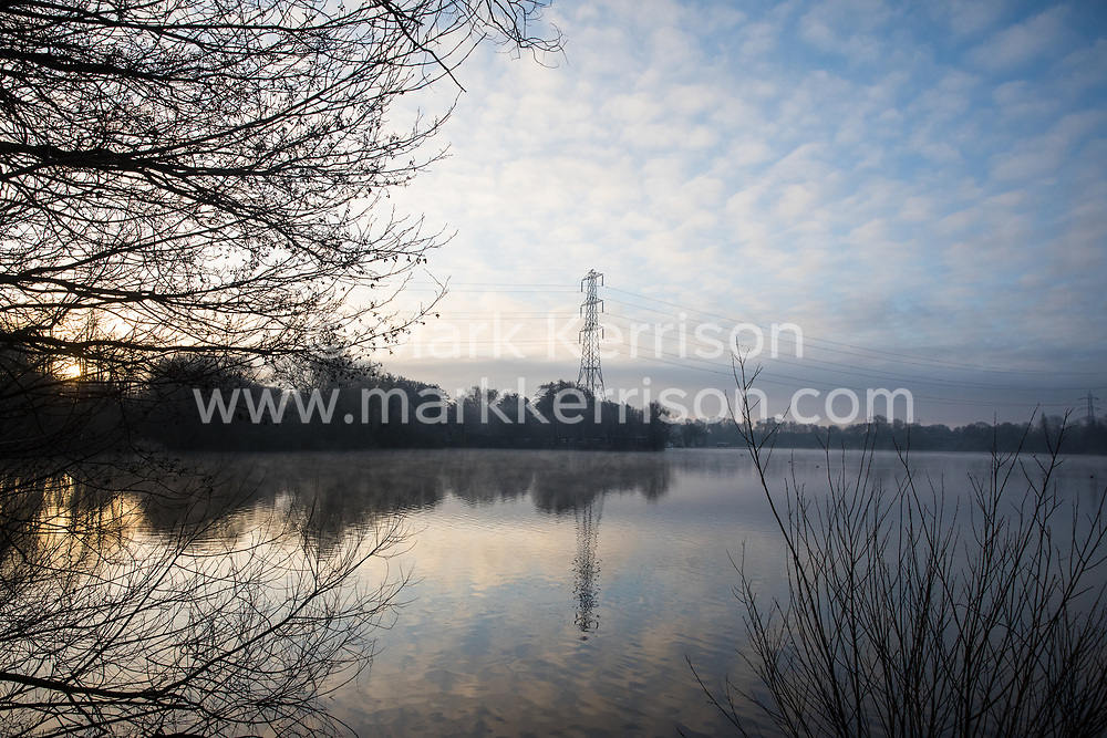 Harefield, UK. 21 January, 2020. The sun rises behind a lake in Colne Valley Regional Park across which a 3.4 km-long viaduct would be constructed should plans for the HS2 high-speed rail link be approved.