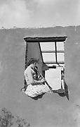 0405-J02 woman playing clarinet in window, Europe.