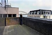 Nederland, Nijmegen, 11-4-2008..Vrouw kijkt via een doorkijkje naar de Waalbrug met rechts hotel courage aan de Waalkade...Foto: Flip Franssen
