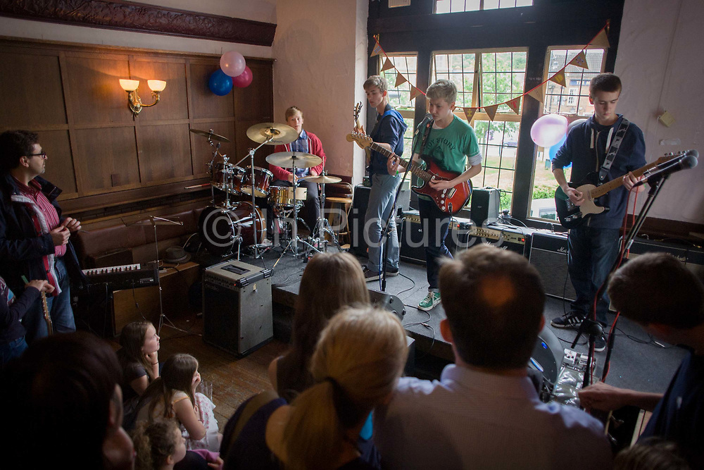 A teenage 4-piece band of drums, bass and two lead guitars perform in front of parents in an upstairs pub room in south London. 15 year-old lads play their own songs and covers by other musical artists. The audience look on as the boys play their instruments on a slightly raised stage in this room lit by daylight. Small girls sit on the floor looking impressed and mums and dads watch proud of their adolescent boys. The gig is a regular showcase organiused by their guitar teacher to demonstrate their musical skills as songwriters and musicians.