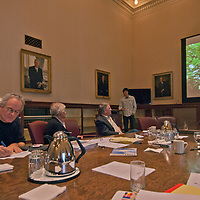 """Young Explorer grantee Andy Maser presents some of his work at the 2012 National Geographic Expeditions Council meeting in the formal boardroom at  Society headquarters in Washington DC. Also pictured are Michael K. """"Nick"""" Nichols, Rick Ridgeway and Donovan Webster."""