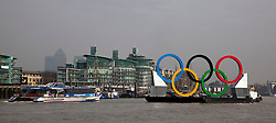 © Licensed to London News Pictures. 28/02/2012. London, England. Giant Olympic rings measuring 11 metres high by 25 metres wide are floated down the River Thames on a barge, marking 150 days to go to the start of the London 2012 Olympic and Paralympic Games. Canary Wharf at back. Photo credit: Bettina Strenske/LNP