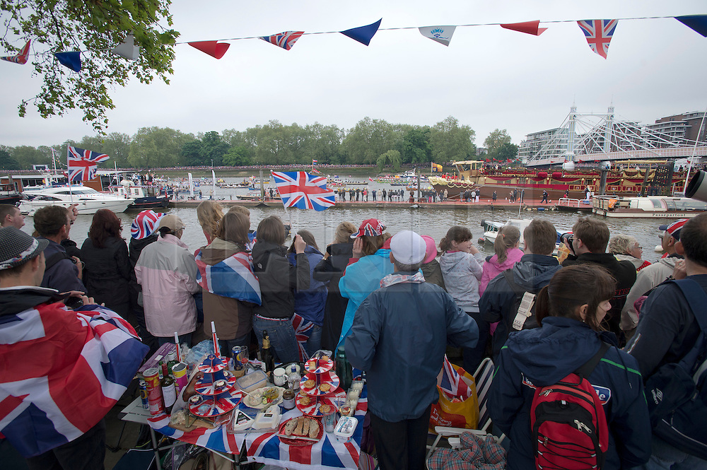 © Licensed to London News Pictures. 03/06/2012. London, UK. Members of the public watch HRH The Queen on board the Royal Barge Spirit of Chartwell from the banks of the River Thames during the Jubilee Pageant on the River Thames, London on June 03,2012 as part of The Diamond Jubilee celebrations. Great Britain is celebrating the 60th  anniversary of the countries Monarch HRH Queen Elizabeth II accession to the throne . Photo credit : Ben Cawthra/LNP