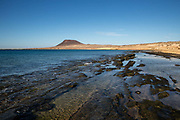 Gentle waves break on exposed volcanic rock at low tide on 23rd November 2020, on Playa Del Salado on La Graciosa island off Lanzarote, Spain. .
