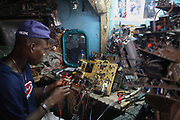Alaba International Market. Julius Paul, a TV repair man at Alaba Market.  His speciality is Sharp televisons. New and old - and a lot of non-working electronic goods such as TVs and computers come in to the market via Lagos harbour from the US, Western Europe and China. This picture is part of an undercover investigation by Greenpeace and Sky News.  A TV-set originally delivered to a municipality-run collecting point in UK for discarded electronic products was tracked and monitored by Greenpeace using a combination of GPS, GSM, and an onboard radiofrequency transmitter placed inside the TV-set.  The TV arrived in Lagos in container no 4629416 and was found in Alaba International Market and bought back by Greenpeace activist. The TV was subsequently brought back to England and used as proof of illegal export of electronic waste. A number of individual are currently on trial in London in connection with illegal exports(Nov 2011)