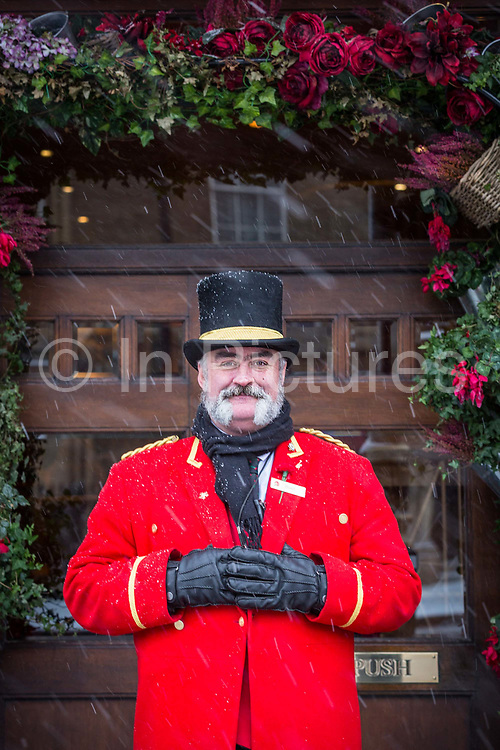 A hotel concierge from The Grosvenor Hotel along Buckingham Palace Road following the arrival of Storm Emma which is set to bring further widespread disruption to many parts of the UK on 2nd March 2018 in Covent Garden, London, United Kingdom. Freezing weather conditions dubbed the Beast from the East brings snow and sub-zero temperatures to the UK.