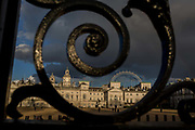 The capitals landmark, Horseguards is seen through railings in St. Jamess Park, on 21st March 2017, in London, England. Horse Guards is a large Grade I listed historical building in the Palladian style in London between Whitehall and Horse Guards Parade. The first Horse Guards building was built on the site of the former tiltyard of Westminster Palace during 1664. It was demolished during 1749 and was replaced by the current building which was built between 1750 and 1753 by John Vardy after the death of original architect William Kent during 1748.
